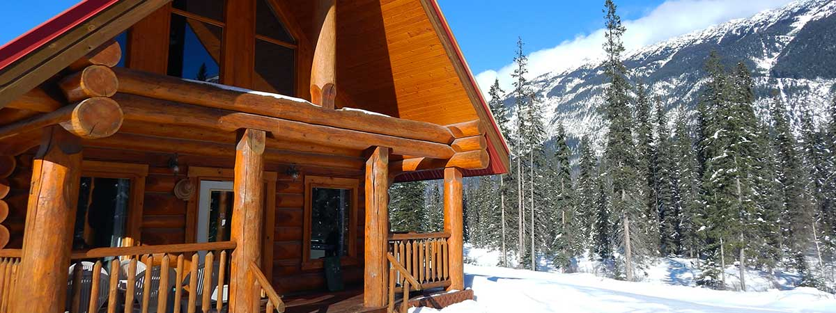 Kicking Horse River Chalets log cabin in winter