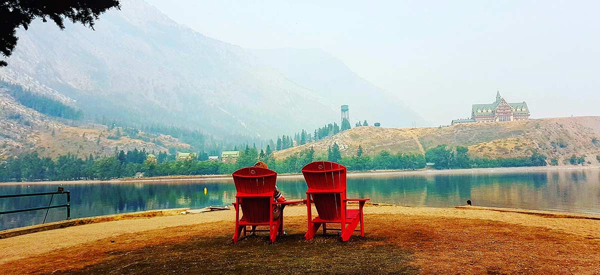 Red chairs on the beach looking towards Waterton Lake